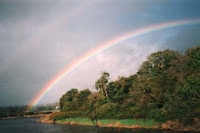 A rainbow above the forest and river