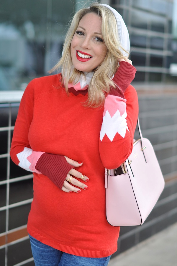 Red hooded sweater with pink and white on sleeves.  Pink Kate Spade purse.
