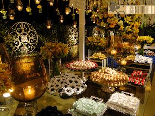 velas vidros âmbar, forminhas personalizadas, bandejas de prata e vidro, cascata de flores amarelas, arranjo foral alto