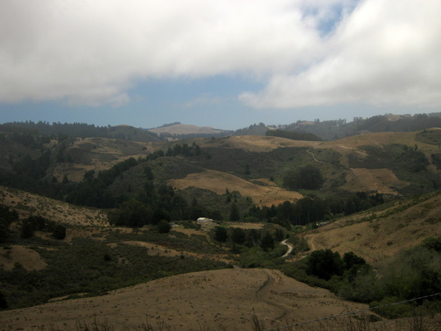 View of blue sky below the marine layer, above the dry rolling hills, from Lobitos Creek Road