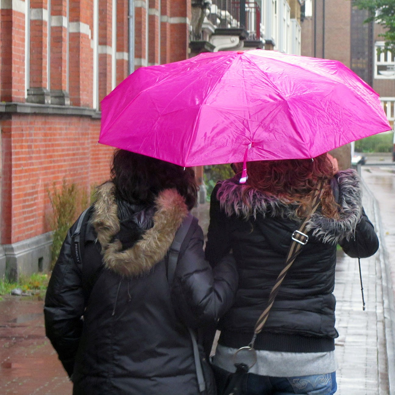 two girls under a pink umbrella