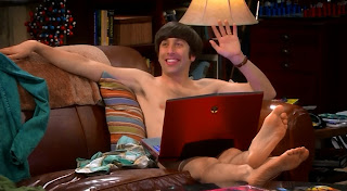 Howard sitting naked in Sheldon's spot on the couch. Howard's groin region is covered by Sheldon's laptop.