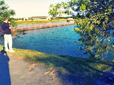 No canto superior esquerdo da imagem aparece de perfil um homem de jeans, camiseta e mochila nas costas fotografando um lago cortado por uma ponte de madeira em arcos e cercado de frondosas árvores. Ao fundo algumas construções. Fiz questão de deixar a minha própria sombra projetada sobre o chão, gravada na imagem.