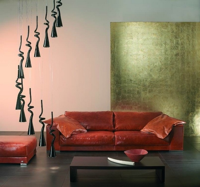 [A living room with a terracotta leather sofa and some gold and black elements]