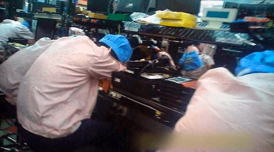 Operários exaustos na linha de produção do iPhone