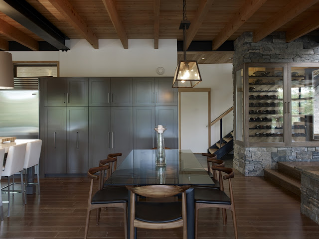 Photo of glassy dining table and wooden chairs in the dining room of the forest house
