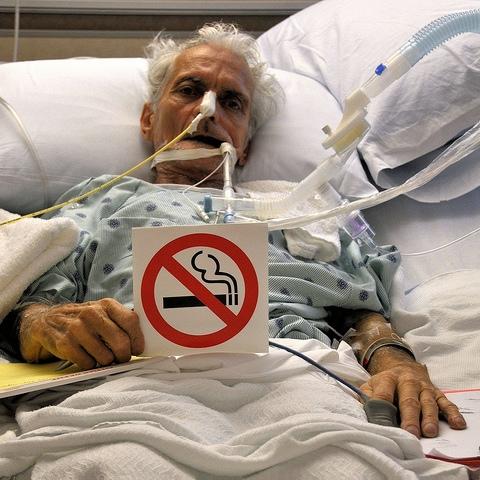 Rygestop, i aller sidste øjeblik. En døende gammel mand med 'Rygning forbudt' skilt