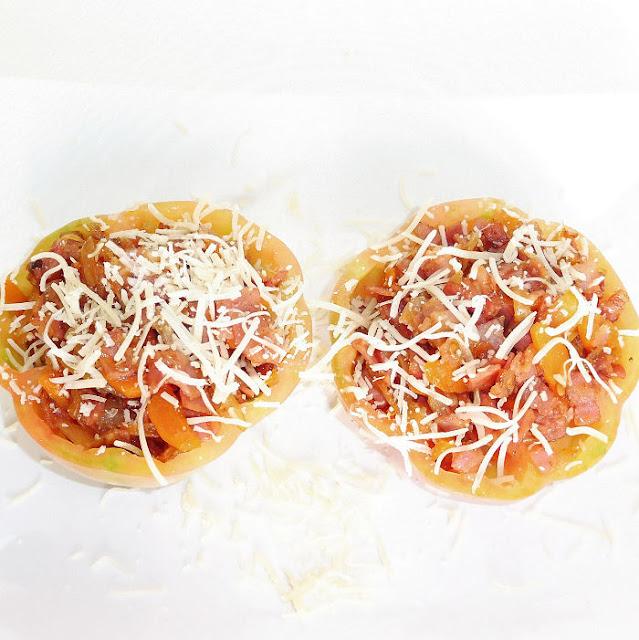 Tomates rellenos con queso rallado sobre un fondo blanco