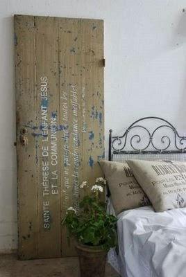 Stare drzwi przecierane na niebiesko z bialymi napisami, oparte o ścianę, jako dekoracja sypialni.