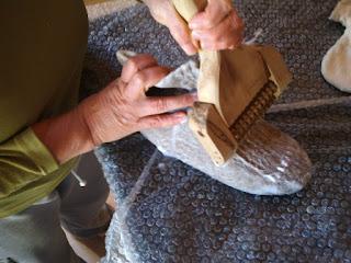 Acessório de madeira dentado feltrando o dorso de pantufa de lã de ovelha