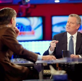 """New York City Mayor Bill de Blasio (right) during an interview last year. On April 22, 2015, de Blasio announced his revamped OneNYC plan, an effort to include poverty reduction in the Bloomberg administration's plan to address climate change, calling it """"a real blueprint of change."""" (Credit: Mayor Bill de Blasio/Facebook) Click to Enlarge."""