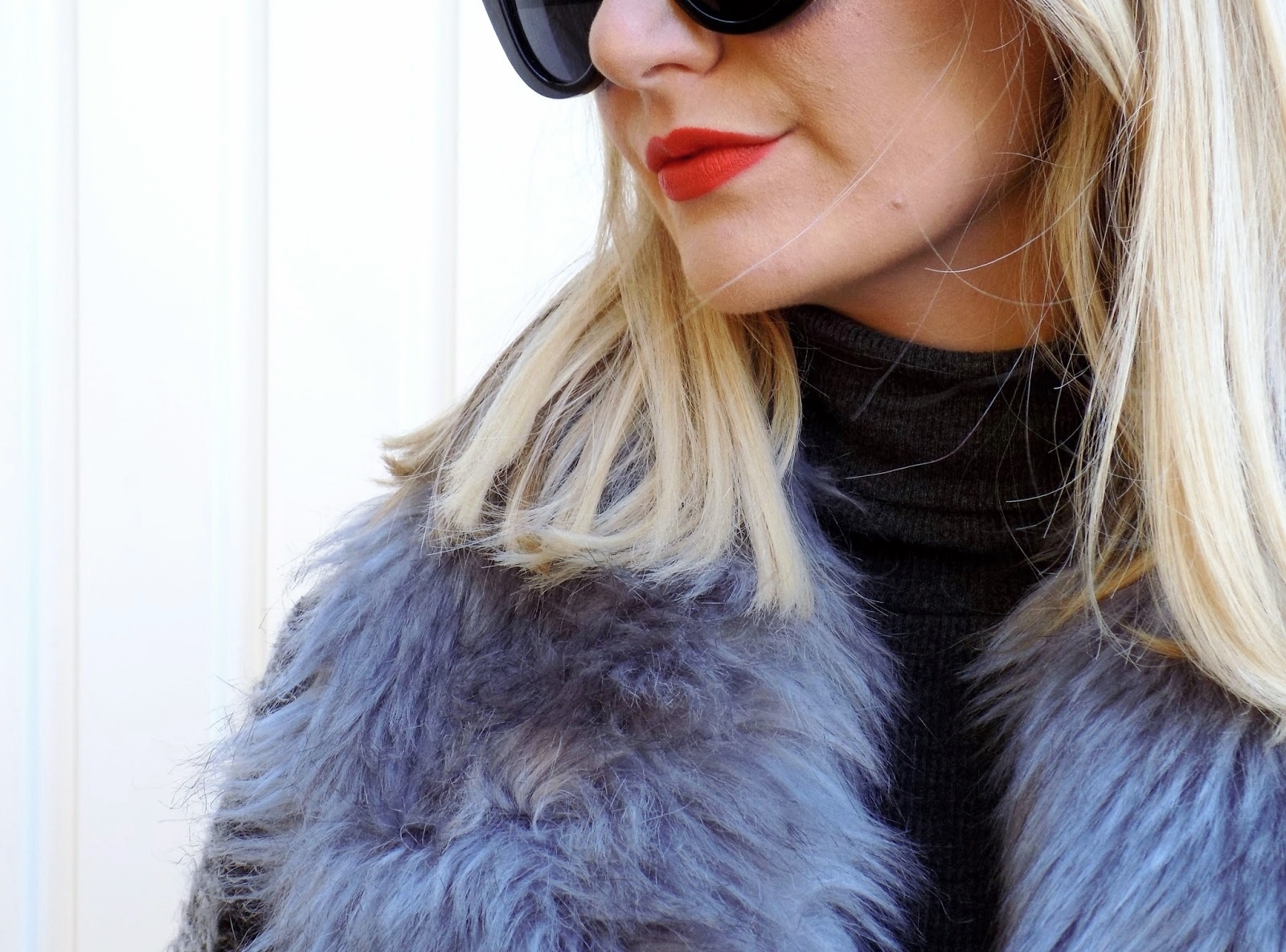 close up of face wearing sunglasses and red lipstick