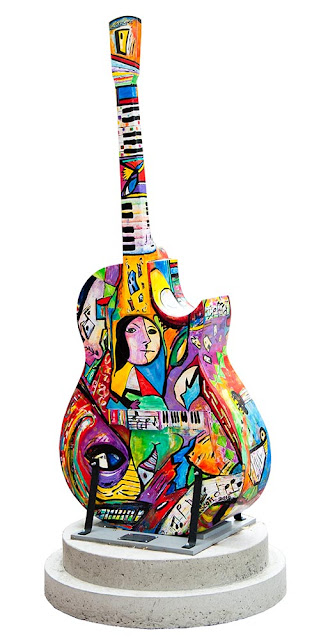 large wooden painted guitar on display in downtown Orillia, the design on this one is multicolour abstract in a picaso-like style