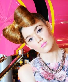 Girl with hair bow and pink lipstick for a photoshoot at an amusement park