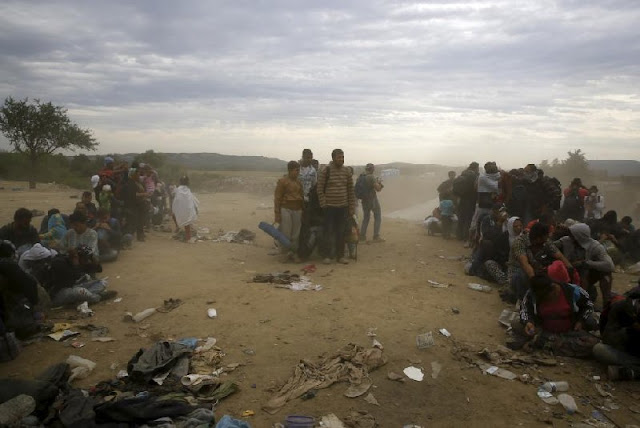 Migrants and refugees wait to cross Greece's border with Macedonia