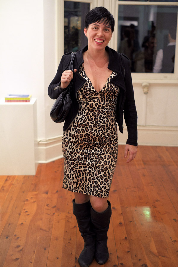 Leopard print dress with plunging neckline, knee boots, black bag and jacket.