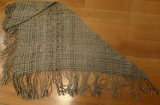 Large triangular shawl with the warp and woof lines visible from a loomed item in tans, brows, white, gray, and black. Very elegant. It has very long fringes on two sides. The remaining side is smooth.