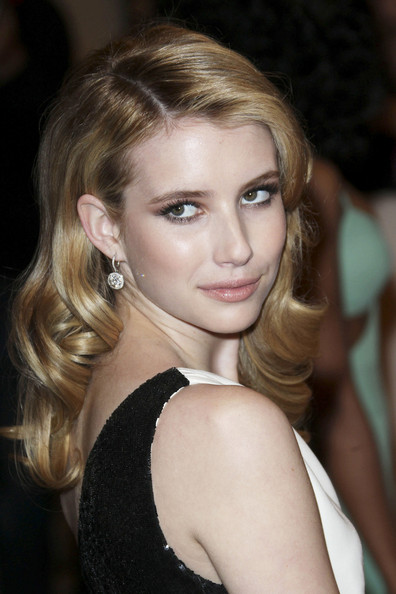 Emma Roberts in a white one-shoulder Michael Kors silk crepe column gown with black Paillette detail and a midriff-revealing cut-out and a pair of Chopard's diamond earrings at the 2011  MET Gala.