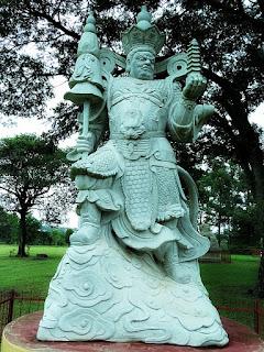 Estátua de pedra com coroa na cabeça e cetro na mão direita.