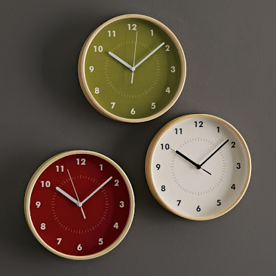 three wall clocks, different colors