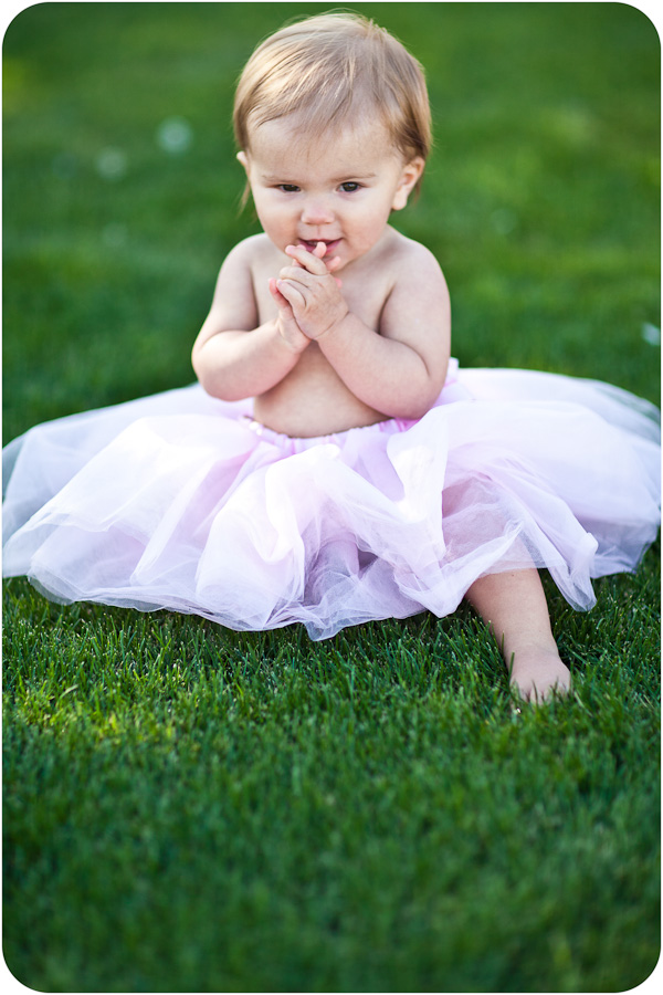 Baby wearing pink tutu with hands to mouth