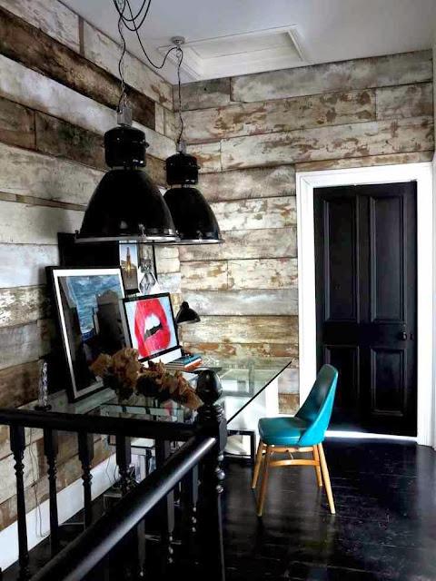 CZarna podłoga, czarne drzwi, czarna poręcz, czarne industrialne lampy, turkusowe krzesło, szklane biurko
