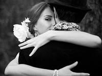 Женщина обнимает мужчину в черном.