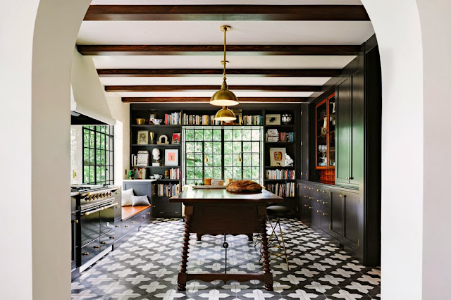Modern kitchen with cement tiles, brass accents, black cabinets, subway tile backsplash and built in bookshelves