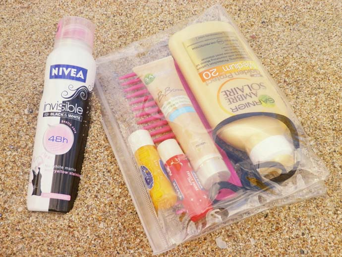 cosmetics I care to the beach: Nivea invisible deodorant, Nivea yellow lip balm with SPF 15, Nivea red cherry tinted lipbalm, Garnier BB cream, Garnier Ambra Solaire SPF 20 body lotion, pink comb, hairband, elastics, all in a clear case