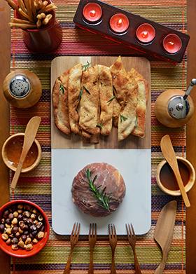 Camembert temperado com alho, azeite e alecrim embalado em fatias de Parma e assado no forno