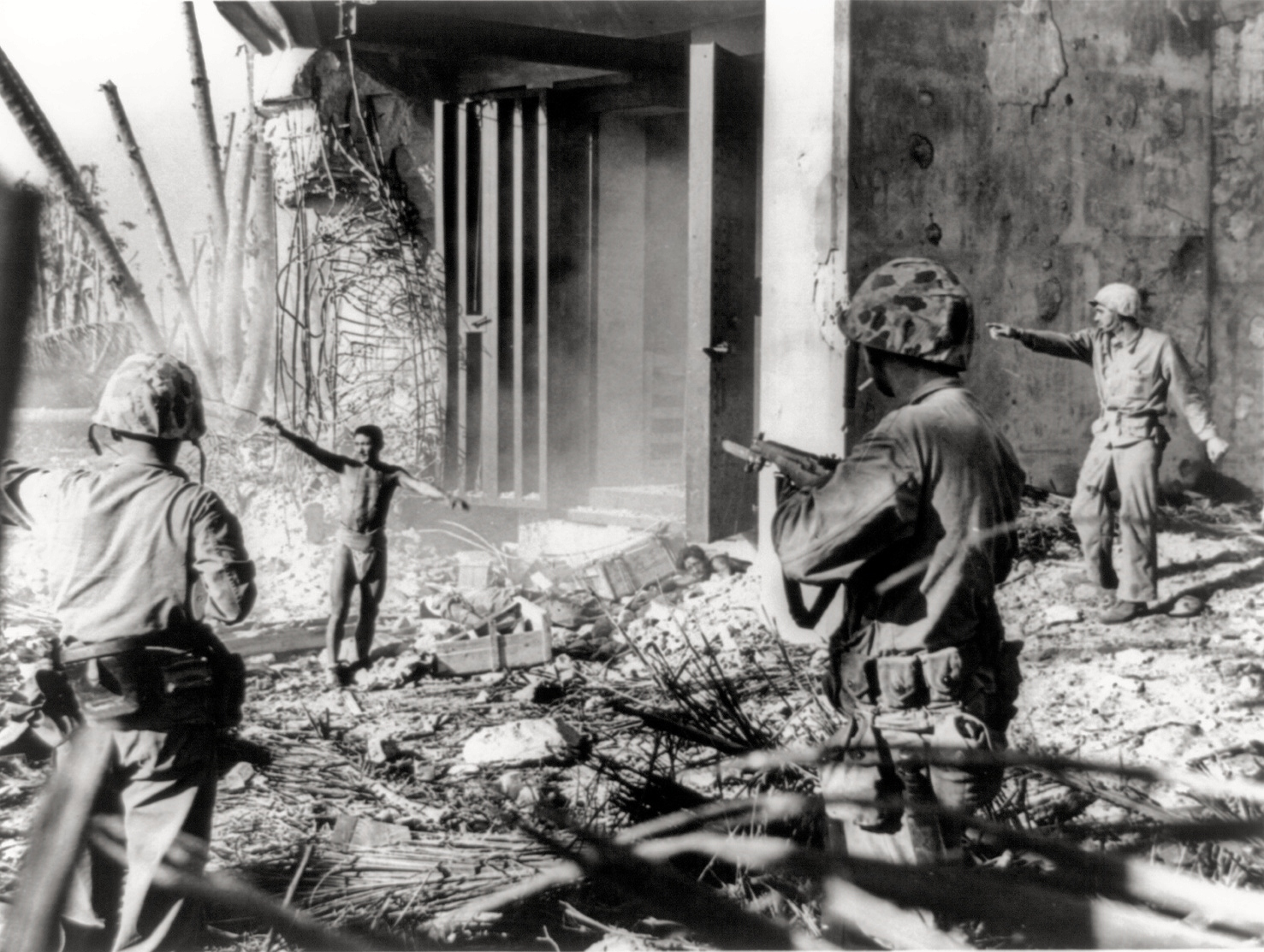 A Japanese soldier surrendering to three US Marines in the Marshall Islands during January 1944.