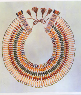 Collar of faience beads depicting corn-flowers, dates, lotus seed-pods, and petals in a pattern derived from garlands of real flowers. Faience bead collars were frequently supplied as favors to guests at banquets. This necklace typifies the technical brilliance of the faience and glass jewelry of the Amarna period (1379-1362 B.C.). It has been suggested that the uniquely gay and joyful quality of Amarna period art and jewelry reflects the sudden appearance of outside influences—possibly attributable to Minoan artists who may have fled to Egypt after the fall of Crete. Excavated from the tomb of Tutankhamen at Thebes.  Diameter, 31 cm. Metropolitan Museum of Art, New York . Rogers Fund