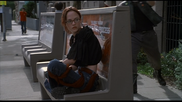 MAY (2002): May (Angela Bettis) sits alone on the bus bench