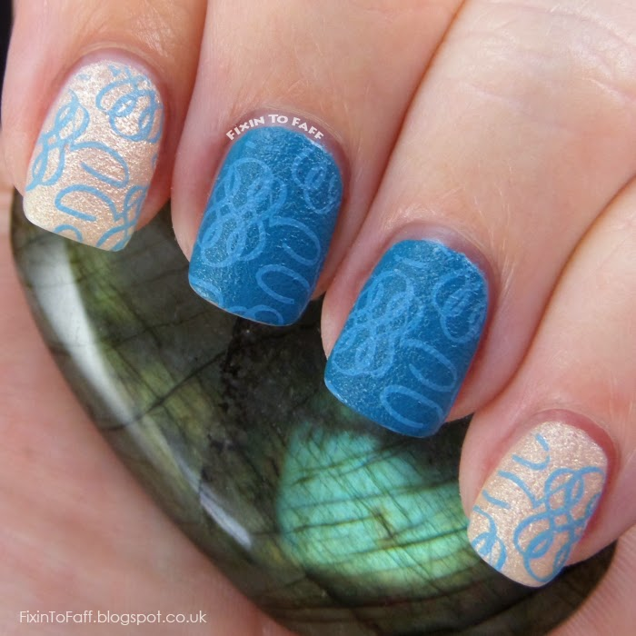 Teal and champagne colored manicure with light blue stamping over textured polish.