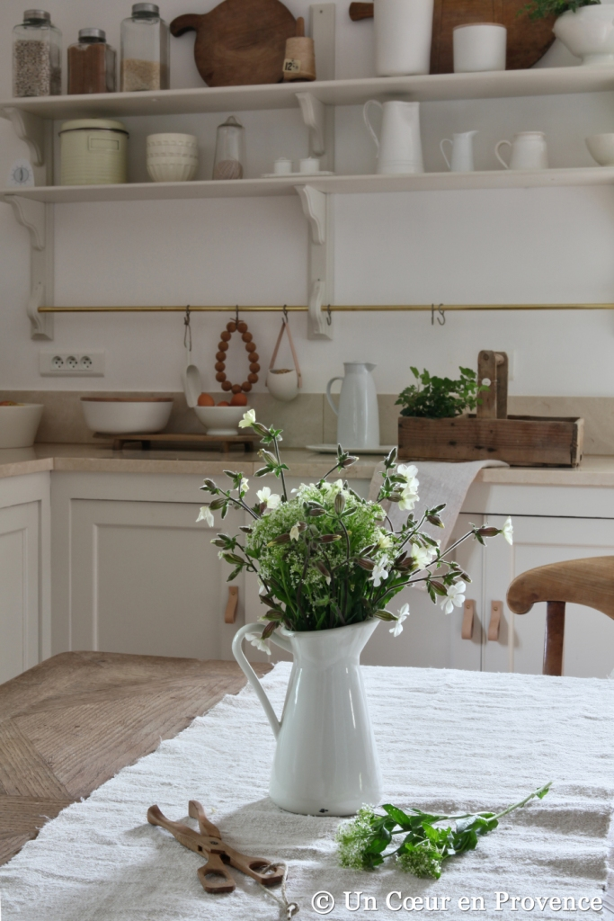 White kitchen with natural wood colour, bunch of white field flowers in a 'Ikea' jug