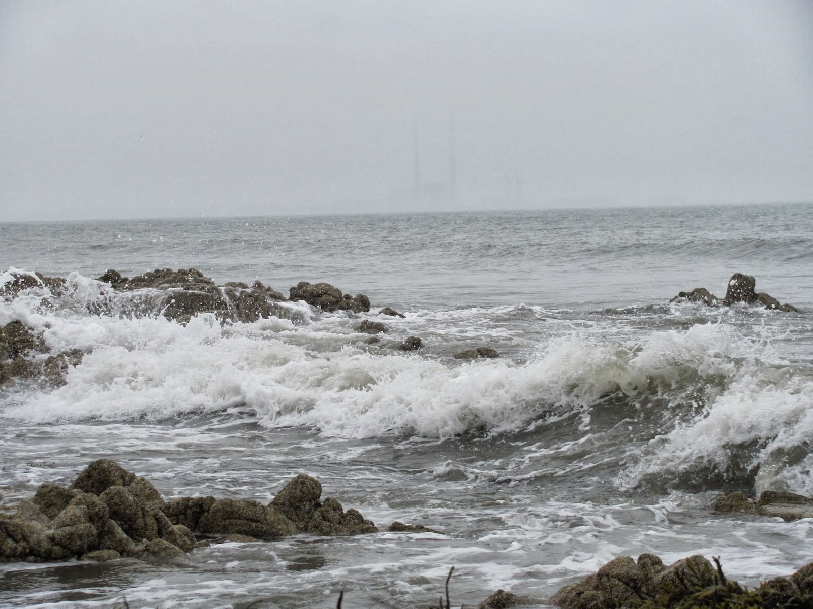 Waves crash from the grey waters of Dublin Bay at Seapoint Beach, Dun Laoghaire, Co. Dublin, Ireland