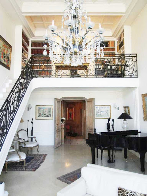 Grand staircase to the second level of a Paris apartment with a chandelier, grand piano and louis chairs