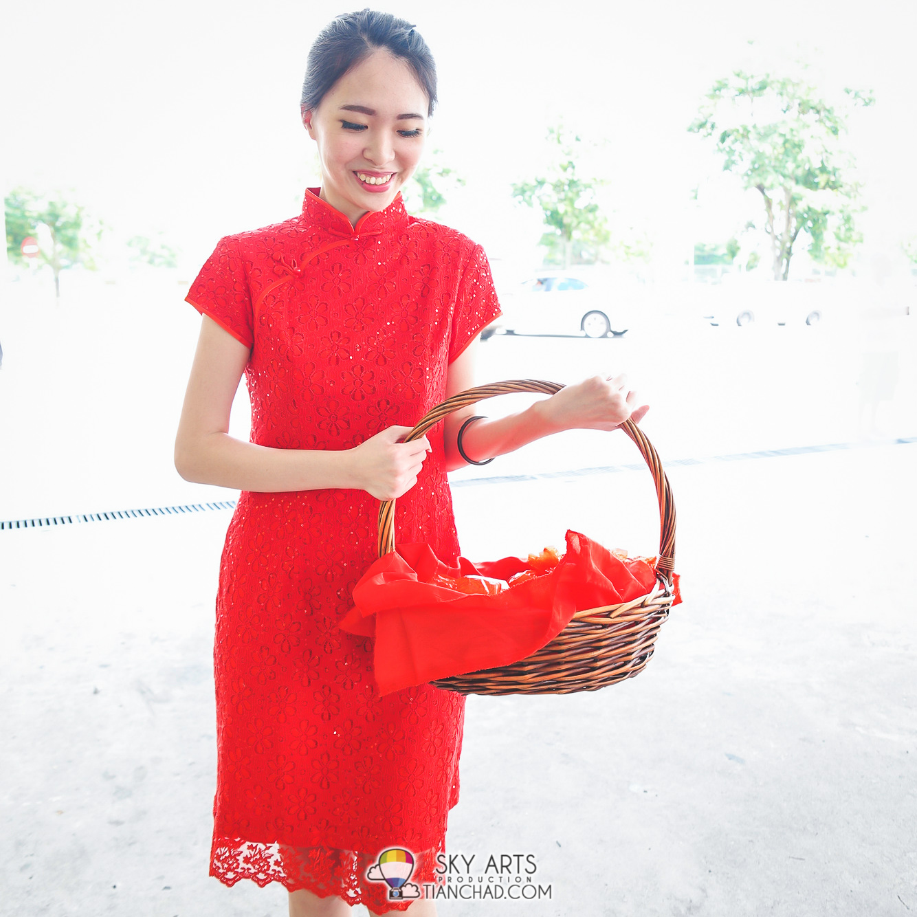 Lady in cheongsam giving out Mandarin Oranges to customer who drop by Petronas Station