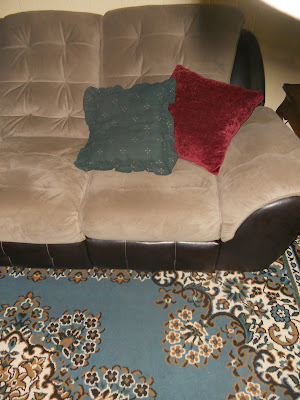 Green and red ugly pillows on couch with blue rug