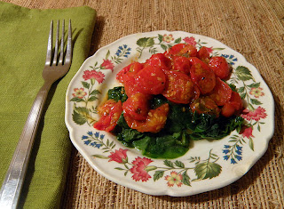 Plate of roasted tomatoes over greens