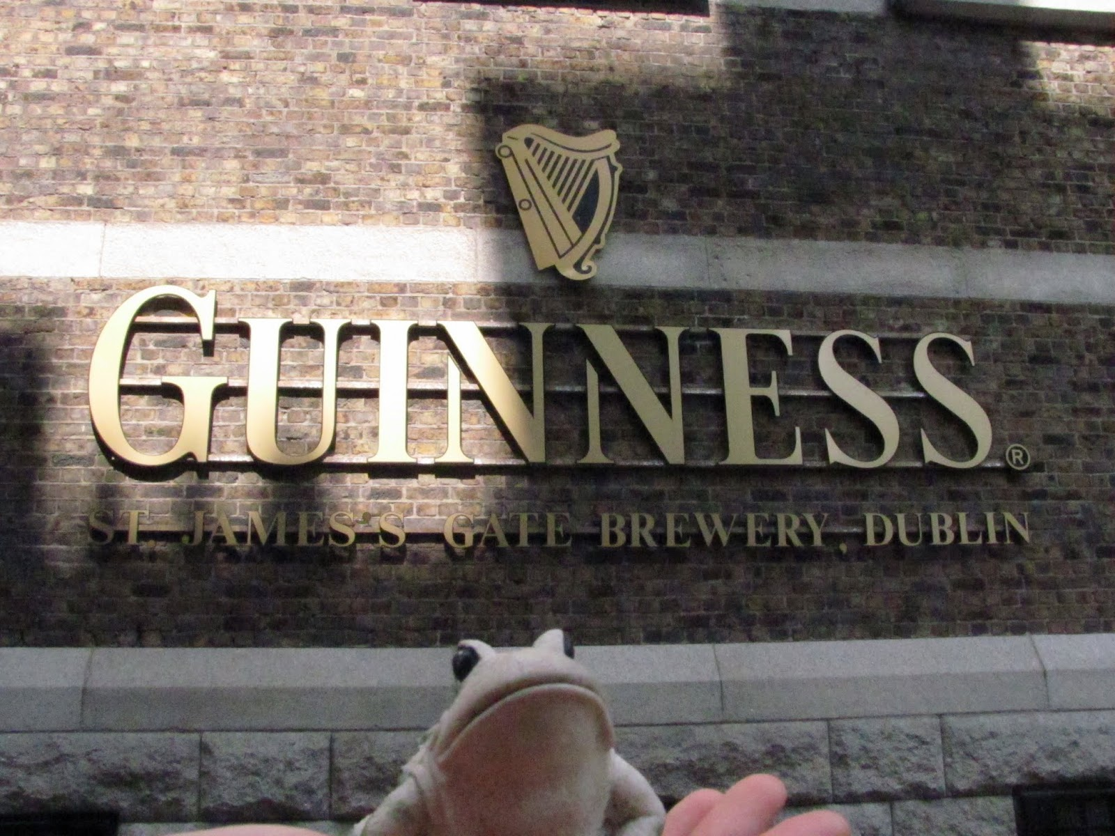Frog poses in front to the entrance to the Guinness Storehouse, Dublin, Ireland