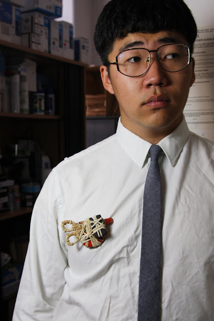 Man in an office wearing a brooch made from scissors and elastic bands.