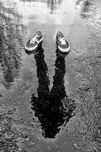 Imagen en blanco y negro de unos zapatos vacíos, sobre un piso mojado y desde los cuales se proyecta una sombre, como si los calzara