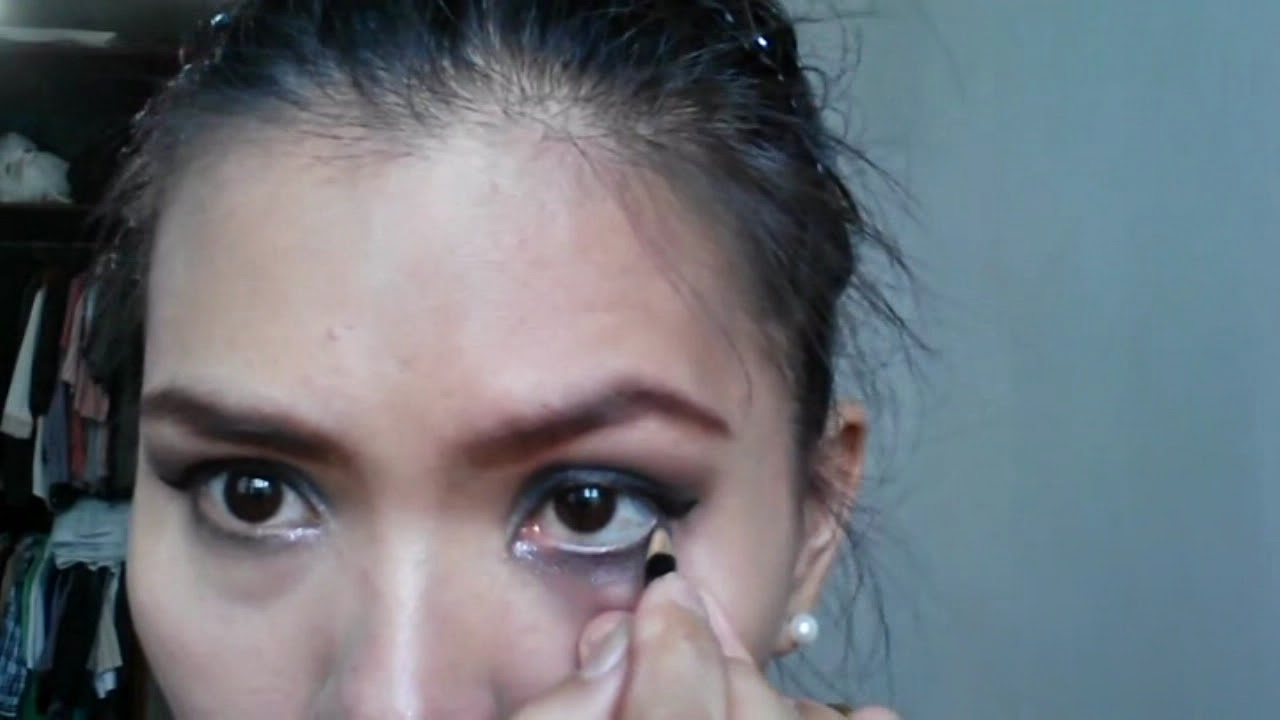 Black Smokey Eyes Makeup Tutorial. Lady putting makeup on her eyes. Lining her waterline with black givenchy eyeliner
