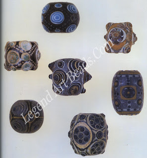 """This remarkable group of seven Chinese eye beads from the """"Warring States """"period (481-221 B.c.) are some of the most technically complex glass beads ever created. Possibly influenced by Phoenician and Roman beads imported into China at this time (Bead Chart 465), these heavy beads are distinguished by their lead-barium content. The layered-glass technique, often with geometric pat-terns formed of dotted lines and sometimes seen with more protruding """"horned"""" eyes than are shown here, is a Chinese contribution to the bead type.' These beads were collected by William Charles White, a Canadian missionary who became the first Anglican bishop of Henan Province. Top bead: diameter; 1.9 cm."""