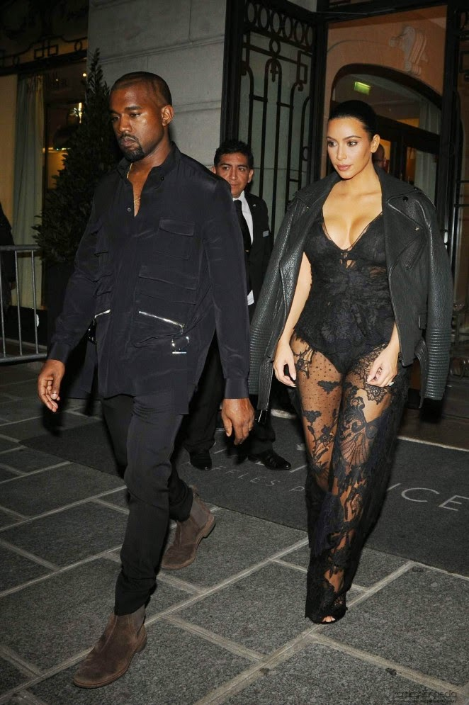 Kim Kardashian wears a plunging black lace jumpsuit to the Givenchy Spring/Summer 2015 Paris Fashion Week Show