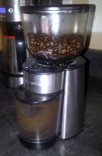 This is a stainless steel coffee grinder with plastic bin for the grounds
