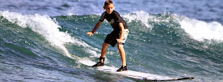 Aloha Beach Camp camper surfing at Zuma Beach in Malibu. Campers between the ages of 5 and 14 will learn to surf at camp.