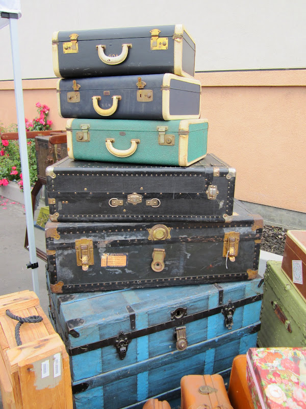 Stack of three vintage suitcases on two black chests on top of a blue steamer trunk
