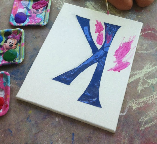"""paints on paper plates and white canvas with the letter """"K"""" taped off being painted on"""